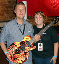 Tim shows off his new Jim Beam guitar, autographed by Daughtry.