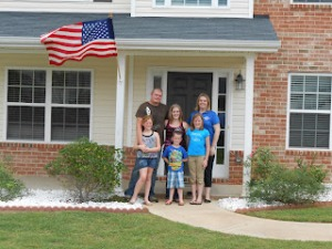 The Biddles in front of their new home with Andrea Kephart from Operation Homefront.