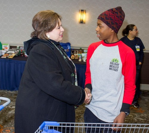 A young volunteer gives back to our military families at Holiday Meals for Military 2013