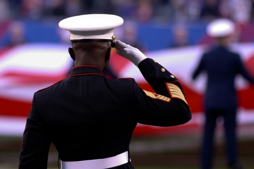 EAST RUTHERFORD, N.J. -- Marine Sgt. Maj. Samuel Heyward Jr., recruiting command New York sergeant major, salutes as a large American Flag is presented across the field at the New York Giants military appreciation game vs the Dallas Cowboys, here, Nov. 14